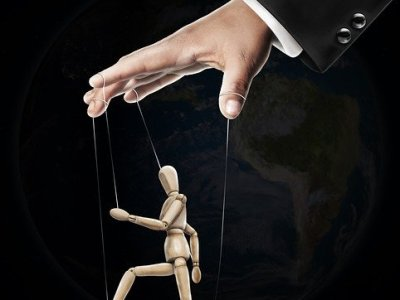 A hand controlling a puppet signifying manipulation of the person