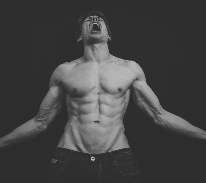 A topless picture of David Graham flexing his muscles, his sixpack on show