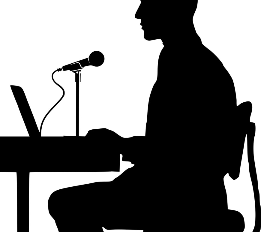 Image of a Man sat at a desk using voice dictation software