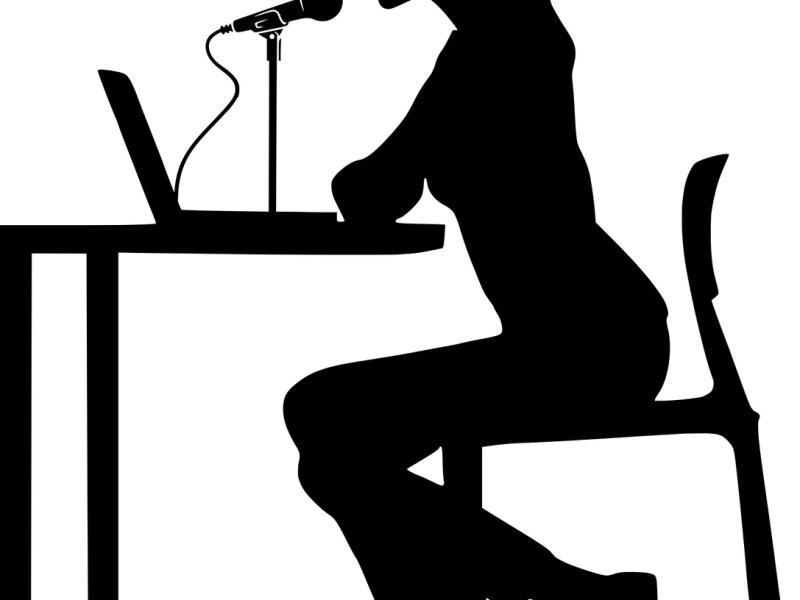 Woman sat at a desk using speech recognition software
